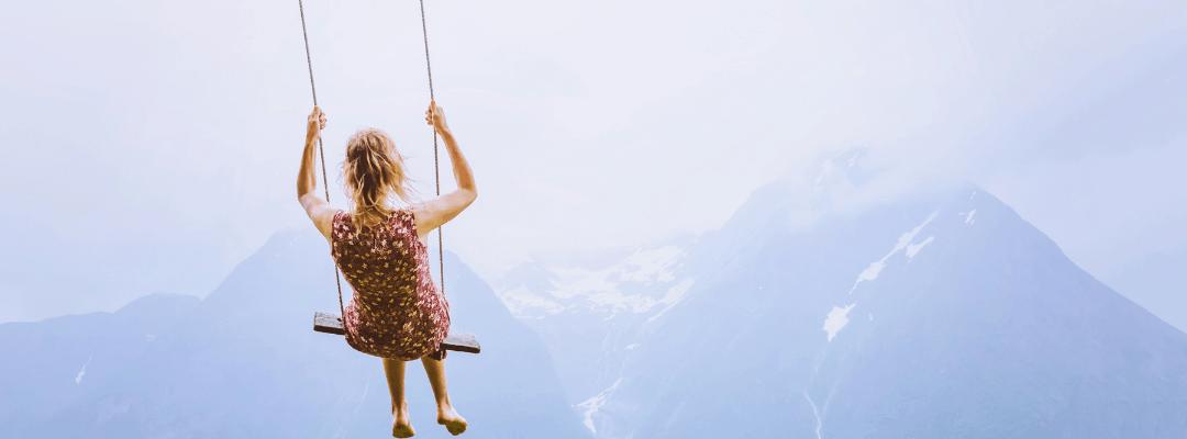 girl in dream on swing in mountains